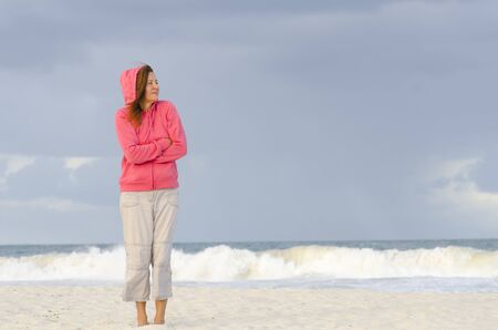 Lonely mature woman at beach wearing warm hooded jumper, isolated with wild ocean and dark storm sky as background and copy space. photo