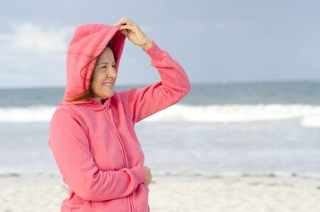 hooded: Portrait attractive senior woman with pink hooded jumper at stormy day at beach, isolated with ocean and dark sky as blurred background and copy space. Stock Photo