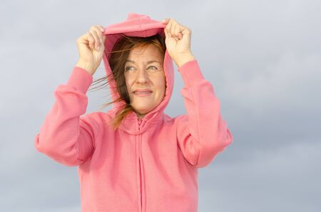 Attractive senior woman in cold weather with pink hooded sweater, isolated with dark rain clouds as blurred background and copy space. photo