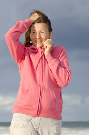 Attractive senior woman in cold weather with pink hooded sweater, isolated with ocean and storm sky as blurred background and copy space. photo