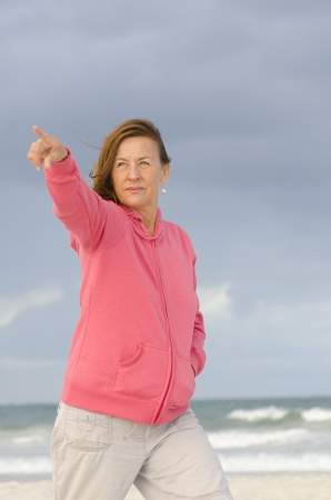 Attractive and confident senior woman in cold weather with pink hooded sweater, isolated with ocean and dark storm clouds as blurred background and copy space. photo
