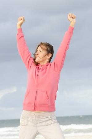 optimismo: Mujer mayor atractiva y segura en tiempo frío con el suéter con capucha de color rosa, aislados con el océano y oscuras nubes de tormenta como fondo borroso y espacio de la copia. Foto de archivo