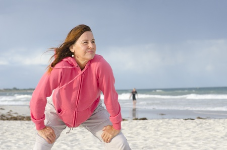 Portrait attractive, happy, confident and positive senior woman in pink sweater at beach, isolated with ocean and dark storm clouds as background and copy space.