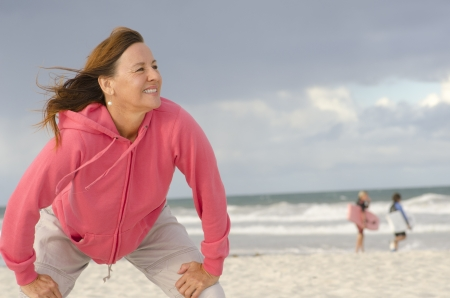 senior exercising: Portrait attractive, happy, confident and positive senior woman in pink sweater at beach, isolated with ocean and dark storm clouds as background and copy space.