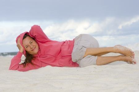 Attractive senior woman relaxed at beach, isolated with ocean and storm clouds as sky background and copy space. photo