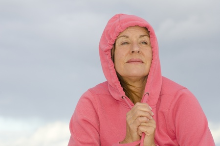 contemplated: Portrait of sad, depressed and contemplated looking mature woman, wearing pink hooded sweater, isolated with dark cloudscape as background and copy space.
