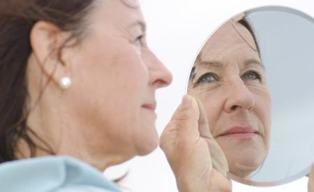 spiegelbeeld: Portret van een aantrekkelijke vrouw van middelbare leeftijd op zoek naar een spiegel, met de nadruk gelegen op het spiegelbeeld.