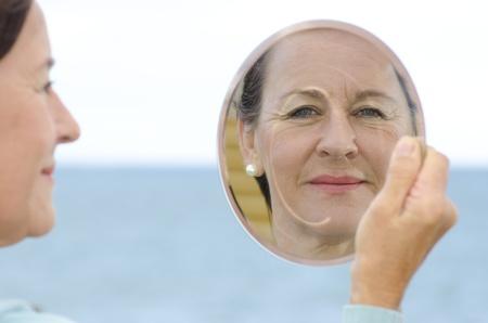 arrugas: Una atractiva mujer madura en busca de unos cincuenta años que mira su imagen en el espejo, aislado con el fondo borroso del océano y el cielo y espacio de la copia.