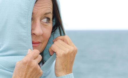 Portrait of a pretty looking mature woman in her fifties wearing a hooded jumper covering her head, with half her face and one eye peeking out, with relaxed and happy facial expression, blurred background of ocean and bright sky as copy space. photo