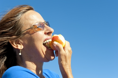 50s adult: Portrait of happy woman keeping healthy and fit by eating fresh fruits, biting in apple, isolated with blue sky as background and copy space.
