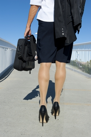 secretary skirt: Businesswoman travelling with laptop, wearing white blouse, dark skirt and high heel shoes, isolated with blue sky as background and copy space.