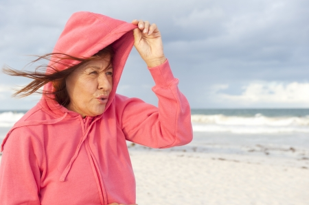 Portrait attractive senior woman with pink hooded jumper at stormy day at beach, isolated with ocean and dark sky as blurred background and copy space. Stock Photo
