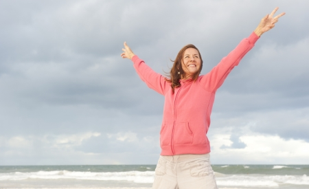 Attractive, happy and confident senior woman in cold weather with pink hooded sweater, isolated with ocean and dark storm clouds as blurred background and copy space.