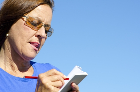 Portrait of concentrated mature woman writing notes on paper with pen, isolated with blue sky as background and copy space. Stock Photo - 15400942