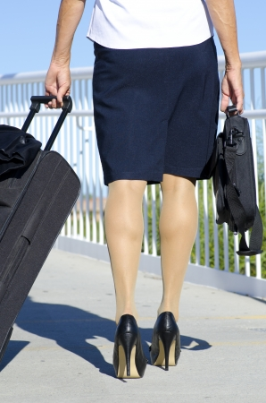 Businesswoman travelling with suitcase and laptop, wearing white blouse, dark skirt and high heel shoes. photo