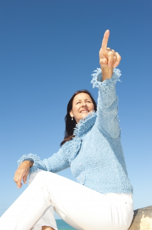 Happy confident and focused mature woman pointing with finger, isolated with blue sky as background and copy space. photo