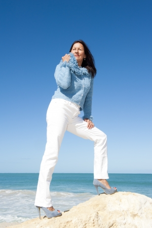 Sexy relaxed senior woman in high heel shoes enjoying active retirement, holiday at sea, with ocean and blue sky as background and copy space. photo