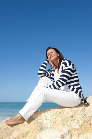 bare women: Happy confident and attractive senior woman  relaxed active retirement holiday at sea, isolated with ocean and blue sky as background and copy space. Stock Photo
