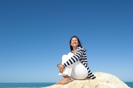 Happy confident and attractive senior woman  relaxed active retirement holiday at sea, isolated with ocean and blue sky as background and copy space. Standard-Bild