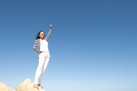 Confident, happy, successful and attractive mature, senior woman on top of rock, mountain, isolated with blue sky as background and copy space. Stock Photo - 15682763