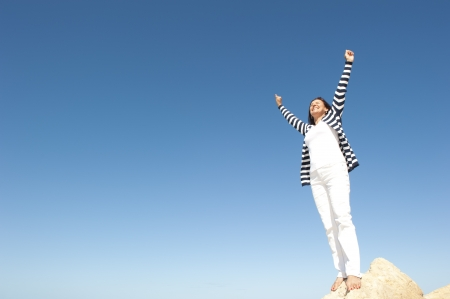 Confident, happy, successful and attractive mature, senior woman on top of rock, mountain, isolated with blue sky as background and copy space. Stock Photo