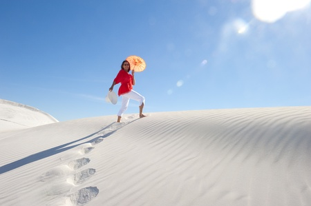Upward view of woman walking up a white desert sand dune in summer heat, with blurred sun rays, clear blue sky as background and copy space. photo