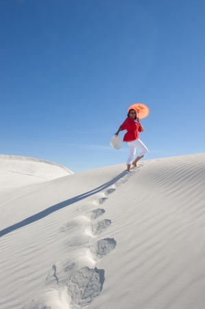 Upward view of an attractive and happy looking mature woman in her fifties walking up a white sand dune
