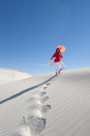 Vista verso l'alto di una donna attraente e felice guardando matura sulla cinquantina camminando su una duna di sabbia bianca