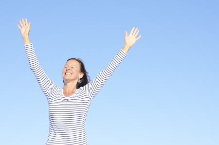 woman looking up: Beautiful happy looking mature woman in cheerful, positive, optimistic pose with arms up, isolated with blue sky as background and copy space.