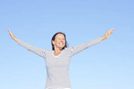 Bella donna felice guardando matura in allegro, positivo, ottimista posa con le braccia in su, isolato con cielo blu come sfondo e copia spazio.
