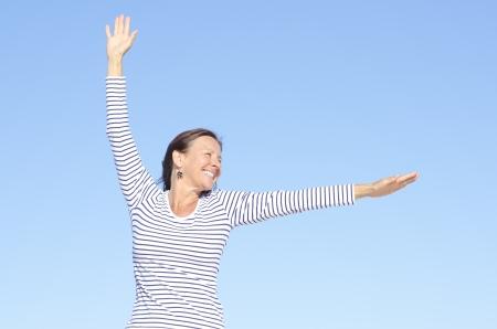 Hermosa mujer madura feliz mirando alegre, positiva, optimista actitud con los brazos arriba, aislado con el cielo azul como fondo y espacio de la copia. Foto de archivo - 15443587