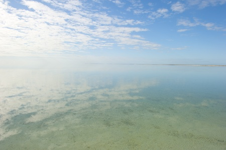 Peaceful clear and smooth ocean surface with optical reflection of low flying clouds over horizon, with endless sea, coastline and and blue sky as background and copy space. photo