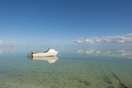 anchoring: Small white boat anchoring at peaceful calm day in shallow water of Shark Bay, Western Australia, with mirror-like reflection of clouds on the oceans surface, blue sky as background and copy space.