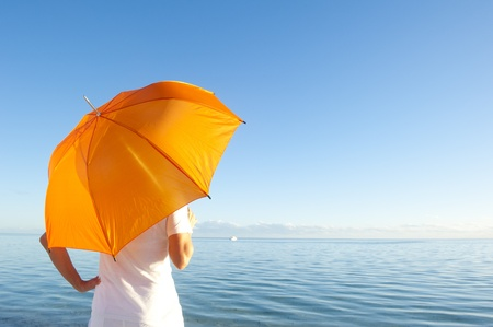 western australia: Confident woman in white shirt and pants standing with orange umbrella over shoulder at peaceful ocean at Shark Bay, Western Australia
