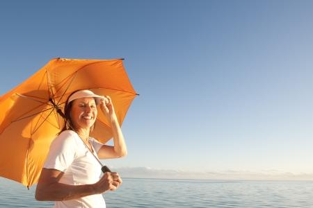 Portrait of attractive mature or senior woman happy and cheerful posing with bright orange umbrella Standard-Bild