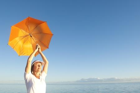 Confiado mujer con camisa blanca y pantalones de pie con el paraguas anaranjado por encima del hombro en el océano pacífico en Shark Bay, Western Australia Foto de archivo - 15443489