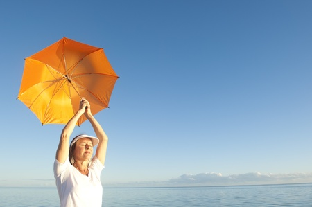 Confident woman in white shirt and pants standing with orange umbrella over shoulder at peaceful ocean at Shark Bay, Western Australia