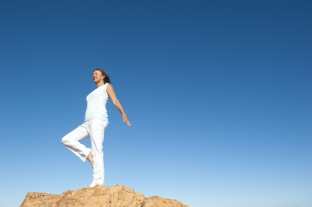 Attractive and fit matue woman standing confident and concentrated on top of a rock, balancing and exercising on one leg, isolated with blue sky as background and copy space. photo