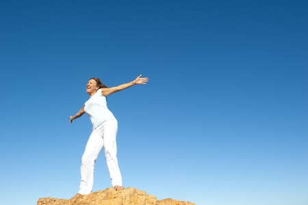 Attractive and joyful mature woman with open arms standing on top of a rock, isolated with blue sky as background and copy space. photo