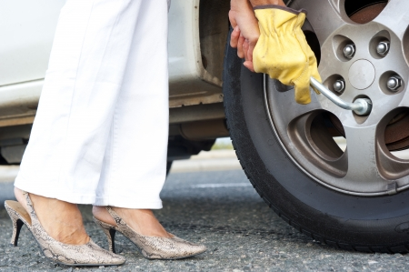 Closeup of womans legs in high heel shoes and hands with gloves plus tool to change tyre at car. Stock Photo - 15586306