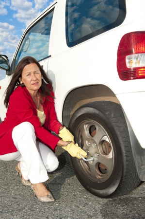 Closeup of unhappy senior woman changing  tyre at car. Stock Photo - 15586308