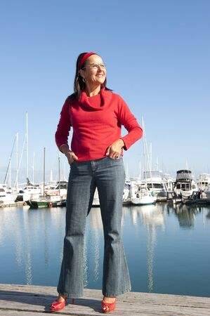 Attractive looking senior woman enjoying relaxed sunny day at marina, isolated with sailing yachts and blue sky as background and copy space. photo