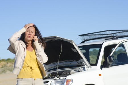 roadside assistance: Stressed mature woman breakdown with car on remote road calling for assistance, for help on mobile phone, isolated with blue sky as background and copy space.