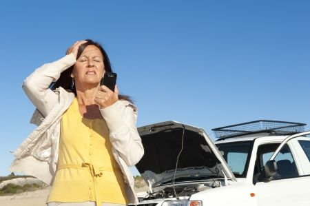 Stressed mature woman breakdown with car on remote road calling for assistance, for help on mobile phone, isolated with blue sky as background and copy space. photo