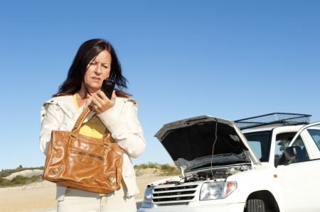 Stressed mature woman breakdown with car on remote road calling for assistance, for help on mobile phone, isolated with blue sky as background and copy space.