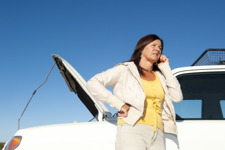 Stressed mature woman breakdown with car on remote road calling for assistance, for help on mobile phone, isolated with blue sky as background and copy space. Stock Photo - 15608363