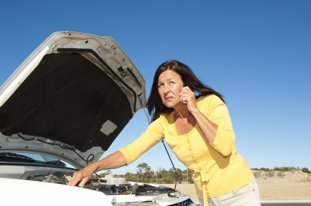 Stressed mature woman breakdown with car on remote road calling for assistance, for help on mobile phone, isolated with blue sky as background and copy space. Stock Photo - 15608276
