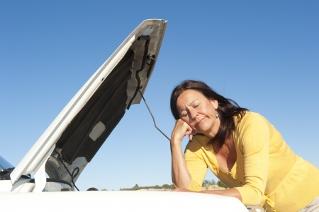 Stressed mature woman breakdown with car on remote road waiting for assistance, for help, isolated with blue sky as background and copy space. photo