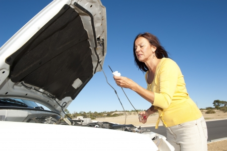 Stressed mature woman breakdown with car on remote road checking oil and waiting for assistance, for help, isolated with blue sky as background and copy space. Stock Photo - 15608366