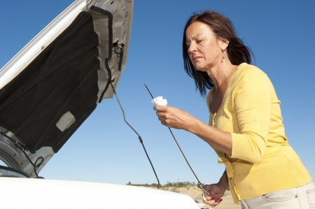 engine bonnet: Stressed mature woman breakdown with car on remote road checking oil and waiting for assistance, for help, isolated with blue sky as background and copy space.